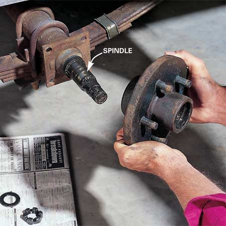 <b>Photo 4: Remove the hub</b></br> Remove the retaining nut and washer, then pull the hub off the spindle. Be careful—the bearings will come out with the hub. Set the bearings on clean newspaper.