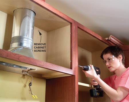 <b>Photo 2: Remove the screws </b></br> Remove the screws to the adjoining cabinets and those in the back of the over-range wall cabinet. Have a helper hold the other side to keep the cabinet from falling.