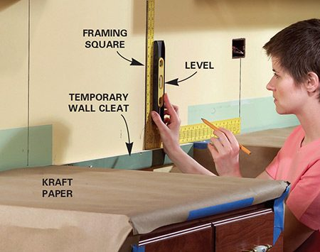 <b>Photo 5: Transfer the layout to the wall</b></br> Draw layout lines on the backsplash as a guide. Screw a temporary wall cleat in the range opening even with the countertop to support the tile. Cover the countertops with kraft paper to protect them from the abrasive mortar.