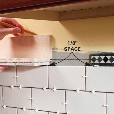 <b>Photo 3: Mark the shelf location</b></br> Center the shelf assembly in the range opening and mark the center of the shelf even with the center of the patterned trim tile.