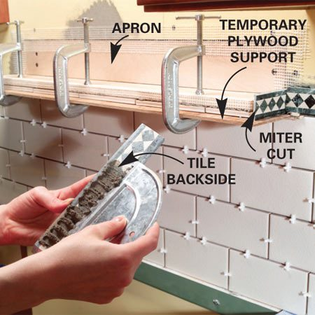 <b>Photo 6:  Screw the shelf to the wall</b></br> Screw the shelf apron to the studs. Clamp a 1/4-in. piece of plywood onto the bottom of the shelf to support the trim tiles.