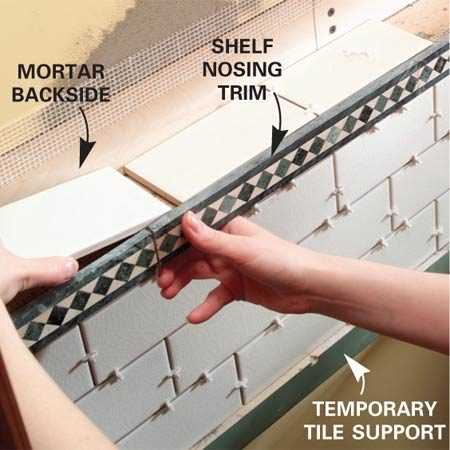 <b>Photo 8: Add the remaining tiles</b></br> Butter the backs of the tiles with your notched trowel. Then set the tile on the top of the shelf once the trim nosing has set.