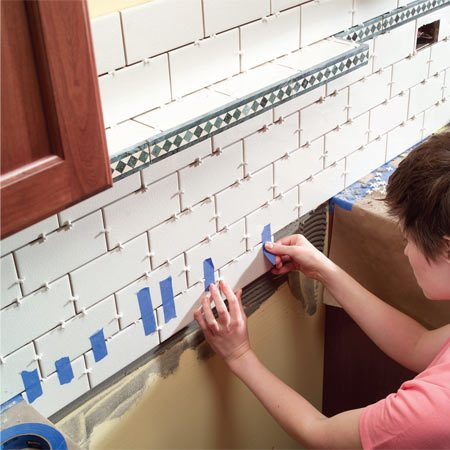 <b>Photo 11:  Tile below the top of the range</b></br> Remove the temporary tile support and set two rows of tile below the top of the range. To keep these tiles from slipping, tape them to the others above that have already set.  (See below for information about building the integral shelf in the photo.)