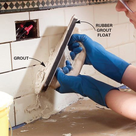 <b>Photo 12: Grout the tile</b></br> When the mortar has set overnight, remove the spacers and scrape out any oozing mortar. Vacuum the tile and grout spaces to remove any hidden clumps of mortar. Mix the grout and push it into the spaces between the tiles with a grout float.