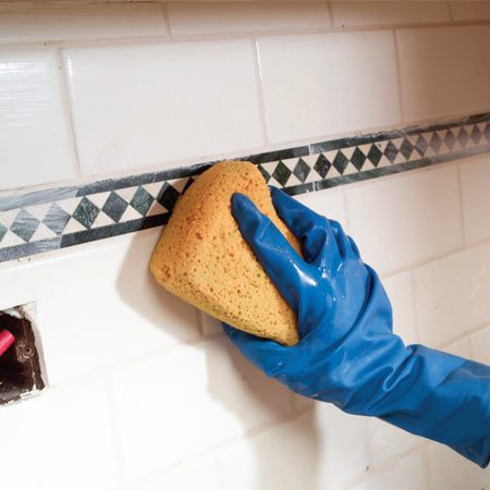 <b>Photo 13: Wipe away excess grout</b></br> Wipe and clean each section as you go with clean water from a bucket. Wring the sponge out well so you're not adding excess water to the grout. Once the grout has set, go over the entire surface with a clean, dry cloth to remove any haze.