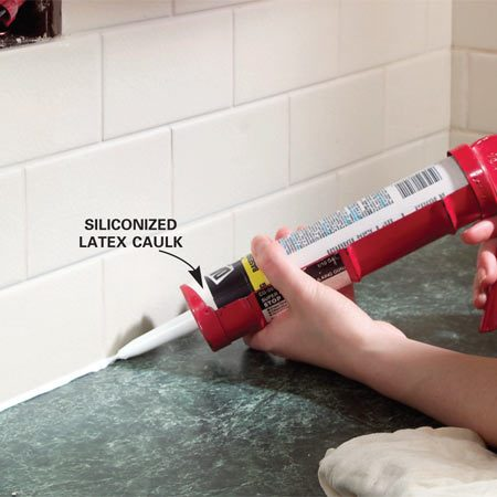 <b>Photo 14:</b></br> Remove the kraft paper from the countertops and use a putty knife to clean the excess grout from the countertop/backsplash joint. Vacuum thoroughly and then apply siliconized latex caulk. Wipe the joint with your finger and then follow with a damp cotton rag for a slim profile joint.