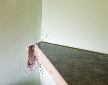 <b>Detail</b></br> Break a hole in the drywall at the miter if the counter fits between two walls.