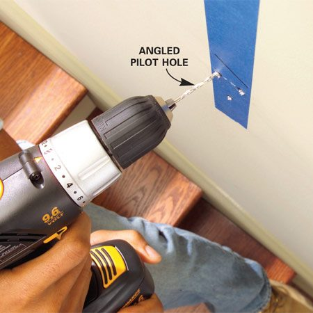 <b>Photo 10: Drill pilot holes</b></br> Drill 1/8-in. pilot holes for the rail bracket screws. You should feel the bit drilling into solid wood. Angle holes slightly toward the center to make sure the screw catch the stud.