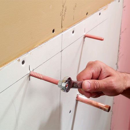 <b>Photo 8: Attach the mounting bolts</b></br> Patch the hole with drywall, then mark the positions for the sink mounting bolts. Drill pilot holes and screw the bolts into the blocking using both mounting nuts tightened against each other.