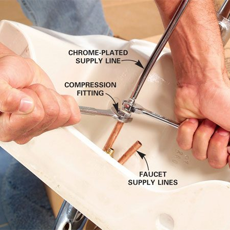 <b>Photo 12: Install supply tubes</b></br> Smear pipe dope onto the threads of the supply line compression fittings and tighten them onto the faucet supply lines.