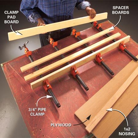 <b>Photo 1: Set up the clamps</b></br> Set up the clamps (one every 8 to 10 in.), the clamp pads and the spacers on your workbench. Adjust the clamps to slightly wider than the shelf and nosing.