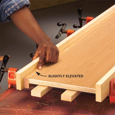 <b>Photo 4: Place the shelf in clamps</b></br> Place the shelf and nosing in the clamps. Feel the joint with your fingertip and adjust the nosing until the top is a hair's width above the plywood as you tighten the clamps.