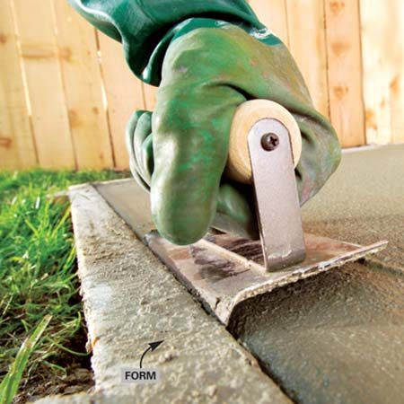 <b>Photo 4: Edge the concrete</b></br> Work the edging tool back and forth, using the edge of the form as a guide. Lift the leading edge slightly. Use long strokes, working the aggregate back until you have smooth, round edges.