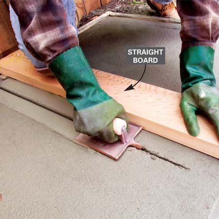<b>Photo 5: Create grooves in the concrete </b></br> Set a straight board along predetermined marks for control joints. Run the groover back and forth against the straightedge until the bed of the tool is riding on the concrete surface.