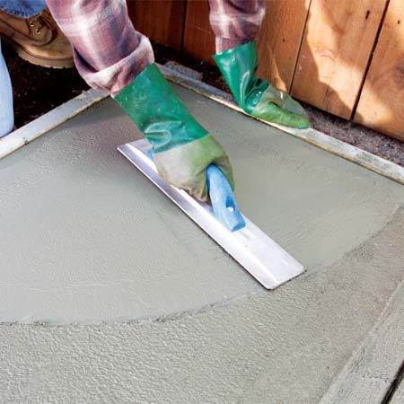 <b>Photo 6: Float the concrete </b></br> Lift the leading edge slightly while you sweep the magnesium float over the concrete in large arcs to compact the surface. Blend in the marks left by the edges of the edger and groover.