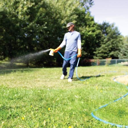 <b>Photo 3: Broad treatment - weeds everywhere</b><br/>A dial sprayer connected to a garden hose kills weeds over a wide area.