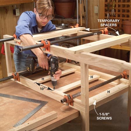 <b>Photo 6: Join the side frames</b></br> Set the two sides upright on a workbench and space them with cross supports at the base and temporary spacers. Then square and clamp them. Predrill, glue and screw on the cross supports (H).