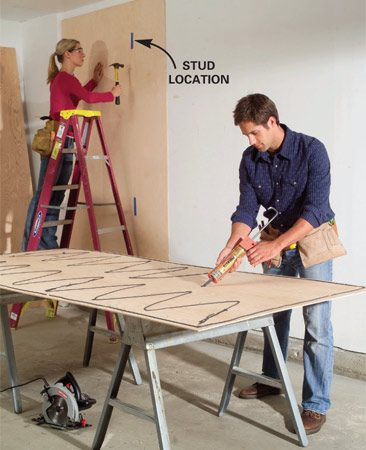 <b>Photo 1: Nail plywood to the studs</b></br> Cover the wall with 1/4-in. plywood. Spread construction adhesive on each sheet, then nail them to studs. Mark stud locations with masking tape.