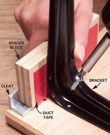 <b>Photo 10: Position shelf brackets </b></br> Position shelf brackets with a 3/4-in. plywood spacer block. Add a strip of duct tape to slightly widen the space so the cleat slips easily onto rails.