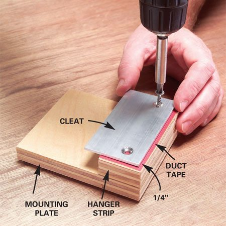 <b>Photo 11: Assemble mounting plates </b></br> Glue a hanger strip to the mounting plate. Then add a strip of duct tape and screw on the cleat 1/4 in. from the top edge.