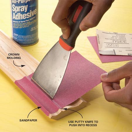 <b>Photo 1: Glue 120-grit paper to the molding</b></br> Spray the molding and the backside of 120-grit sandpaper with spray adhesive. Stick it to the molding, making sure to press it into recesses with the blade of a putty knife.
