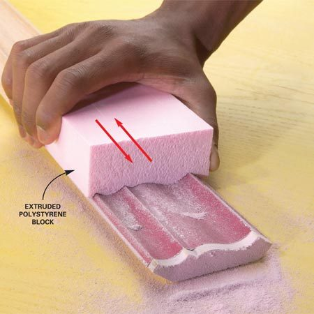 <b>Photo 2: Sand a foam block to the profile</b><br/>Rub a block of rigid foam insulation over the sandpaper until it conforms to the molding&#39;s profile.