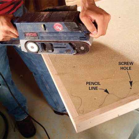 <b>Photo 5: Sand edging flush</b></br> Sand the proud edges of the hardwood nosing flush with the top and bottom of the particleboard. Don't oversand the edges and create a dip. Mark the top surface with a pencil line and sand to it. Fill the screw holes with wood putty and sand them flush with the top.