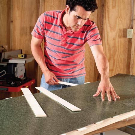 <b>Photo 9: Pull the strips</b></br> Pull the strips out one by one, beginning at the center and working your way out to the edges. Press the laminate into place as you go. Work carefully to get the laminate flat onto the worktop without air pockets.