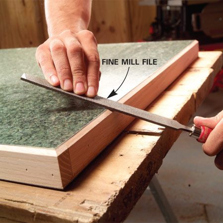 <b>Photo 13: File the edges </b></br> Finish-sand the wood edges with a sanding block and then ease the sharp edge of the laminate with gentle strokes using a fine mill file.