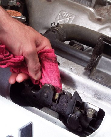 <b>Clean hood latch</b></br> Wipe away grease, dirt and sand with clean rag.