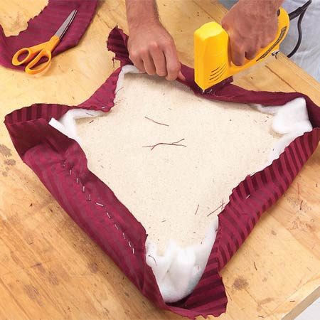 <b>Photo 2: Staple the fabric</b><br/>Staple the fabric at the middle of each side and work toward the corners, stretching the fabric as you go. Stop about 2 in. from corners and leave the corners for last.