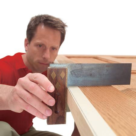 <b>Photo 3: Check your progress</b></br> Stop sanding occasionally to make sure that you're sanding squarely and not creating a beveled edge. Remove the excess wood with a belt sander. Sand right up to the line, but not into it.