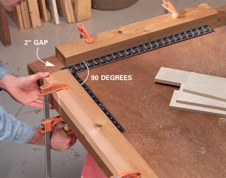 <b>Photo 3: Set up an assembly jig</b></br> Clamp or screw two straight 24-in. 2x4s to the corner of a flat surface to use as an assembly jig. Use a carpenter's square to ensure squareness. Leave a 2-in. gap at the corner.