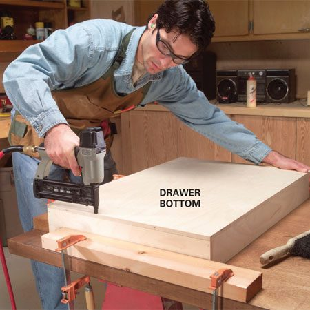 <b>Photo 5: Nail the drawer bottom</b></br> Cut a 1/2-in. plywood bottom to size. Apply a thin bead of glue to the bottom edges, and nail one edge of the plywood flush with a side, spacing nails every 4 in. Then push the frame against the jig to square it and nail the other three edges.