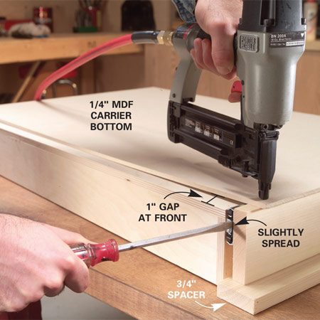<b>Photo 9: Nail the carrier bottom</b></br> Rest the carrier assembly on 3/4-in.-thick spacers, pull the carrier sides slightly away from the drawer, then nail on the carrier bottom (no glue).