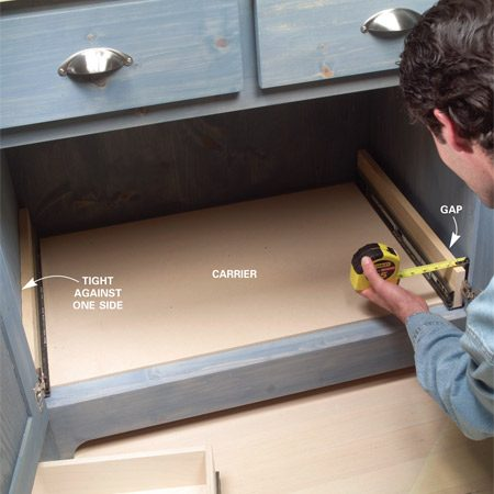 <b>Photo 10: Measure for spacers</b></br> Remove the drawer, tip the carrier into the cabinet and push the carrier against one side. Measure the gap and rip six 3-1/2-in.-long spacers to half of the thickness.