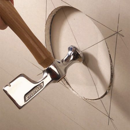<b>Photo 3: Knock out the opening</b></br> Score the paper on the backside, using the pilot hole to center the circle cutter. Then knock out the plug from the front with a little rap from your hammer.