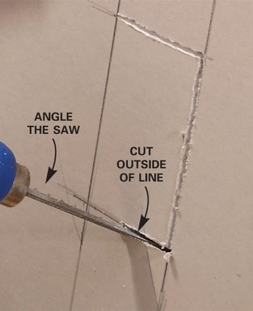 <b>Photo 1: Cut out three sides of the box</b></br> Lay out all four sides of the box and cut through three sides with a drywall saw.