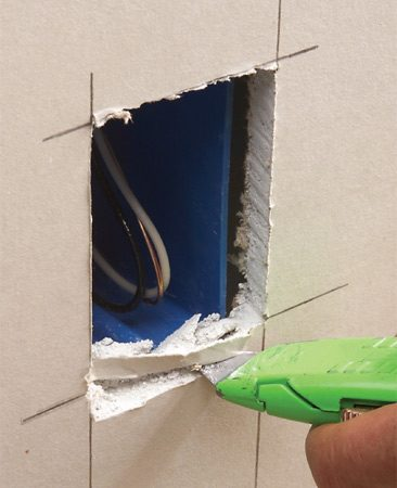 <b>Photo 4: Widen the opening, if needed</b></br> Fasten the drywall with a few screws, then press the cutout over the box. For extra clearance, shave the edges as needed with your utility knife.