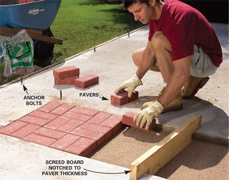<b>Photo 1: Pour the slab and set the pavers</b></br> Pour the concrete base and set the anchor bolts. Screed the sand over a concrete base with a notched 2x4. Set the pavers even with the concrete.