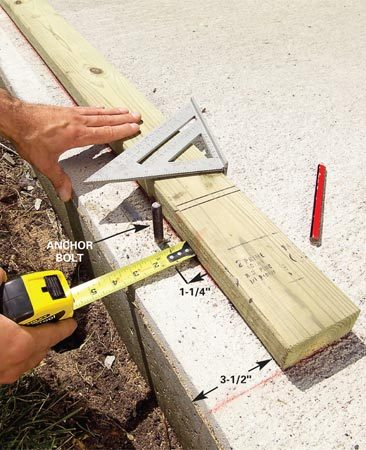 <b>Photo 2: Cut and drill the plates</b></br> Snap lines on your slab to establish the wall plate locations. Set the treated wall plates against the lines and transfer the anchor bolt locations. Drill 5/8-in. diameter holes at the bolt locations.