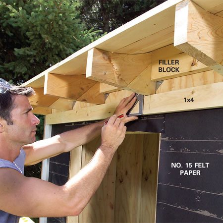 <b>Photo 28: Cut and install rafter trim</b></br> Tack a 1x4 up against the bottom of the rafters and scribe it to fit against the bottom of the filler blocks. Cut the notches with your jigsaw and nail it into place.