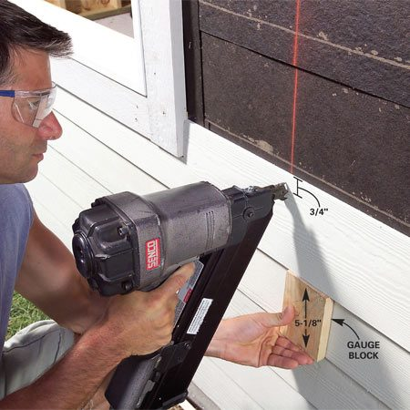 <b>Photo 30: Nail on the siding</b></br> Nail a 5/16-in. x 1-in. starter strip at the bottom edge of the building to create a bevel and nail rows of cement lap siding through the sheathing into the studs. Use galvanized nails to nail the siding within 1 in. of the top of each course. Unlike with conventional wood siding, the nails will all be hidden by the next course. The nails in the top row will be exposed.