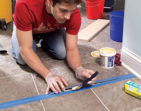 <b>Photo 1: Stick adhesive under the loose flooring</b></br> Protect the floor with masking tape and apply an even coat of adhesive. Then lay wax paper over the seam and press it down with a board and weights overnight.