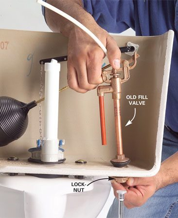 <b>Photo 3: Remove the old valve</b></br> Remove the locknut that holds the valve to the tank. Push down gently on the valve as you unscrew the nut. Pull out the old valve.