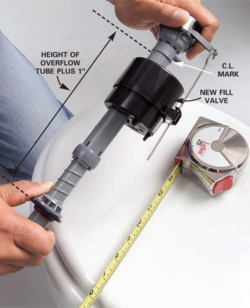 <b>Photo 5: Twist the top of the new valve to adjust the height</b></br> Adjust the height of the new fill valve by holding the base and twisting the top. The height from the base to the CL (critical level) mark should be the height of the overflow tube plus 1 in.