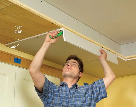 <b>Photo 12: Drywall the underside</b></br> Screw 1/2-in. drywall to the underside of the soffit, leaving a 1/4-in. gap against the wall. Trim the outer edge flush with the plywood.