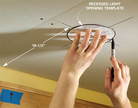 <b>Photo 13: Cut out the openings</b></br>  Mark the exact center of each recessed light 18-1/2 in. from the wall. Position the light template and trace the fixture opening. Cut the opening with a drywall saw.