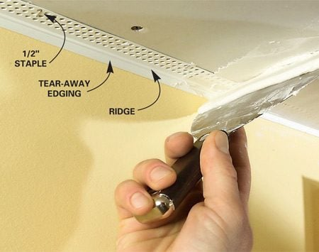 <b>Photo 14: Finish the rock</b></br> Slip the fixed flange of tear-away edging behind the drywall and staple it into place. Fill the edging with taping compound. Tape the butt joints and fill over screwheads. Peel the tear-away flanges free, then sand and paint.