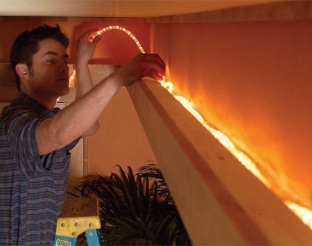 <b>Photo 18: Lay the rope lights</b></br> Install the switched receptacle for the rope lights. Assemble enough rope light length to fill the soffit perimeter. Then plug it in and lay it into the trough.